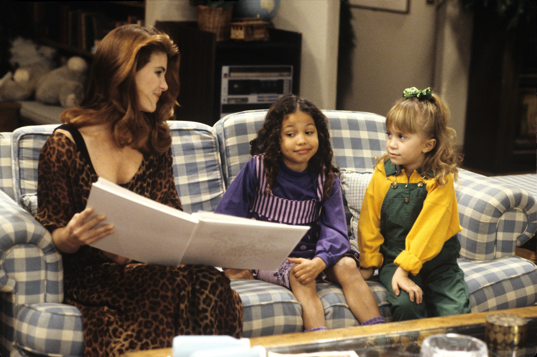 "Lori Loughlin, Jurnee Smollett, and Mary-Kate Olsen sitting on couch in the ""Full House"" living room"