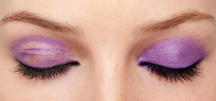 A model wearing the primer on their right eye, and not wearing the primer on the left eye, showing how the primer kept their purple eyeshadow in place.