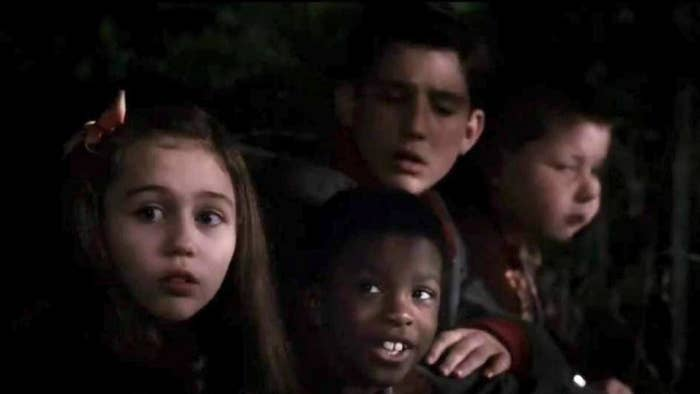 Miley Cyrus surround by other kids in the dark