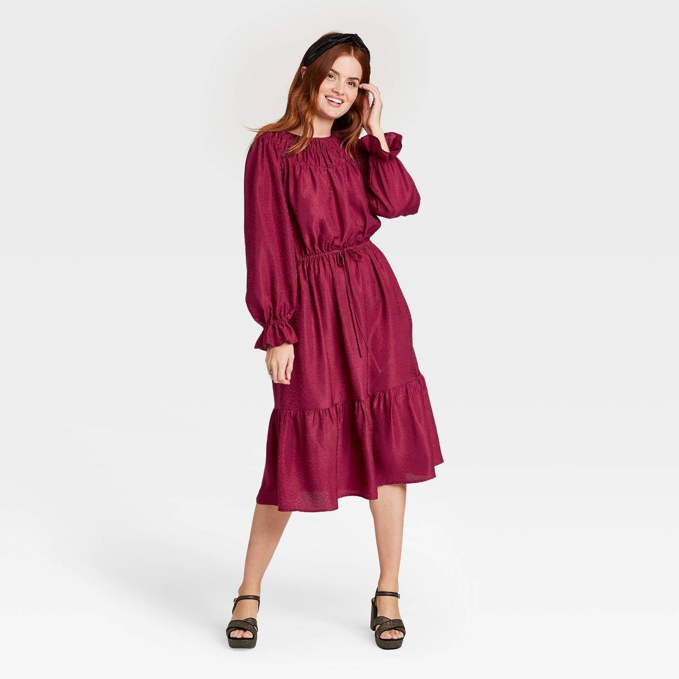 Model wearing magenta midi dress with cinched waist
