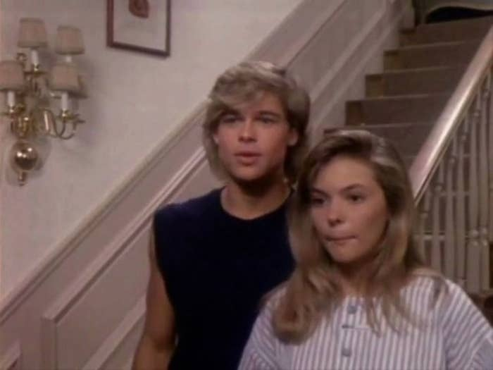"""Screenshot from """"Dallas"""" of Brad Pitt next to a blonde actress in front of a staircase"""
