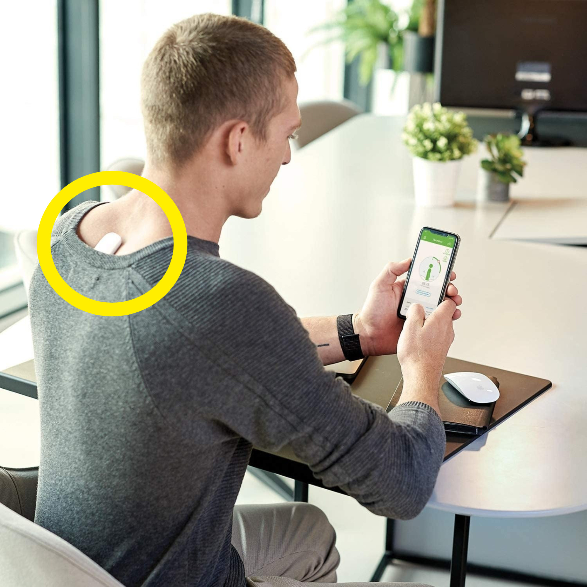 A person wearing the posture corrector on their back while looking at the app on their phone