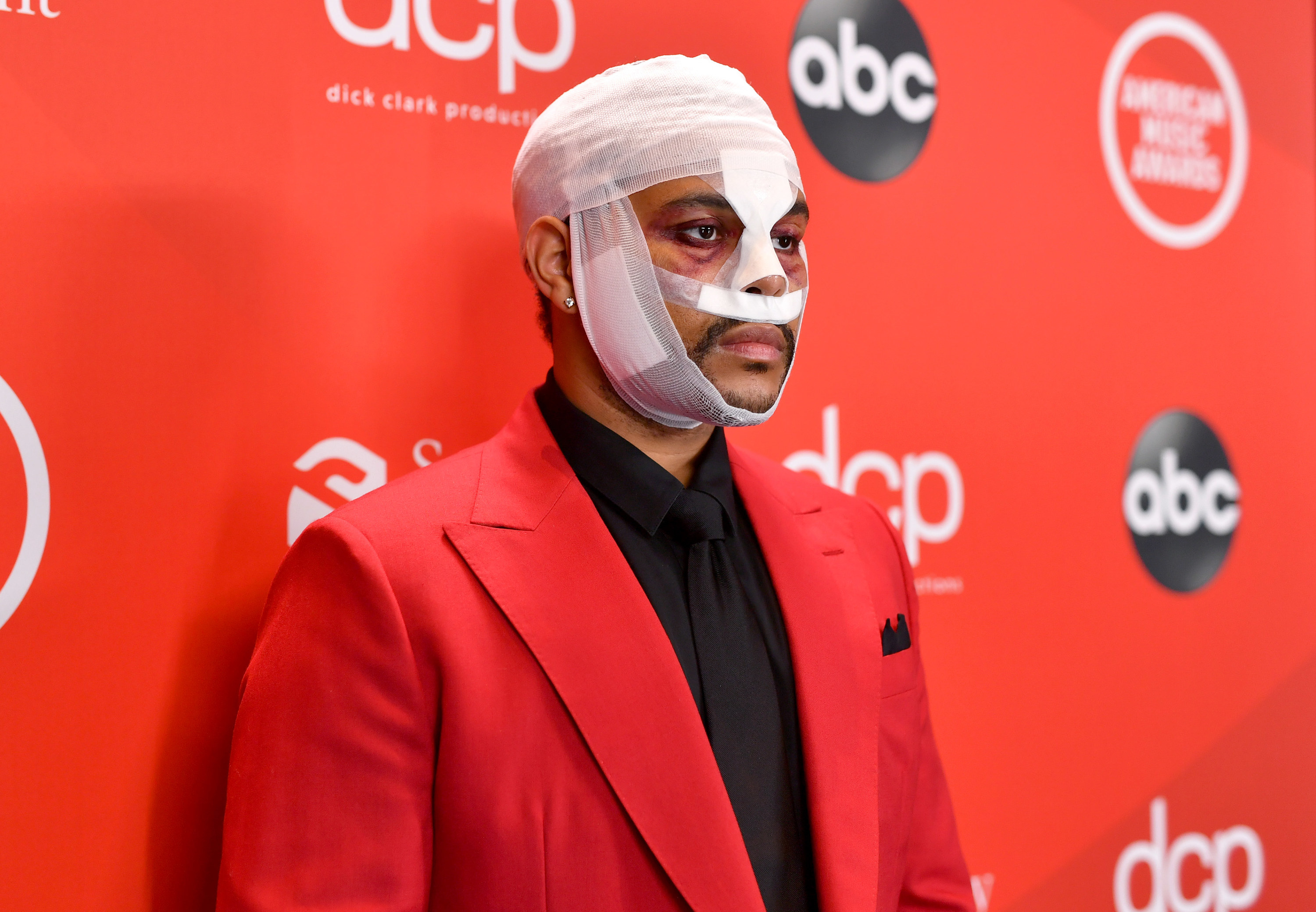 The Weeknd wears face bandages on the red carpet at the American Music Awards