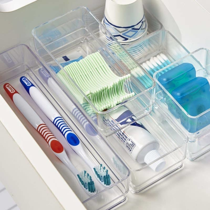 The organizers in a drawer holding toothbrushes, toothpaste, floss, cotton swabs, and cups