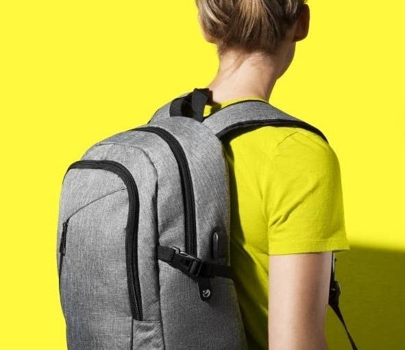 A person wearing the backpack in grey