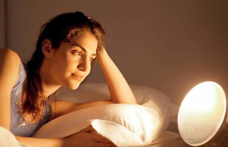 A person using the circular, illuminated lamp