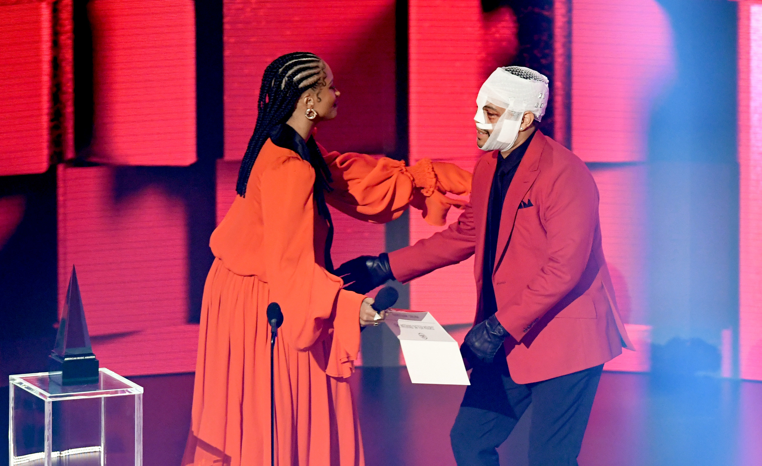 The Weeknd accepts an award from Ciara at the 2020 American Music Awards