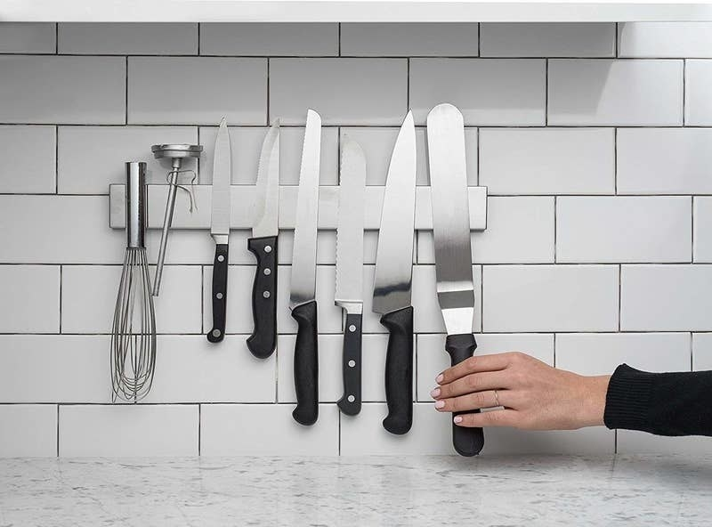 A person reaching for a utensil on the knife strip