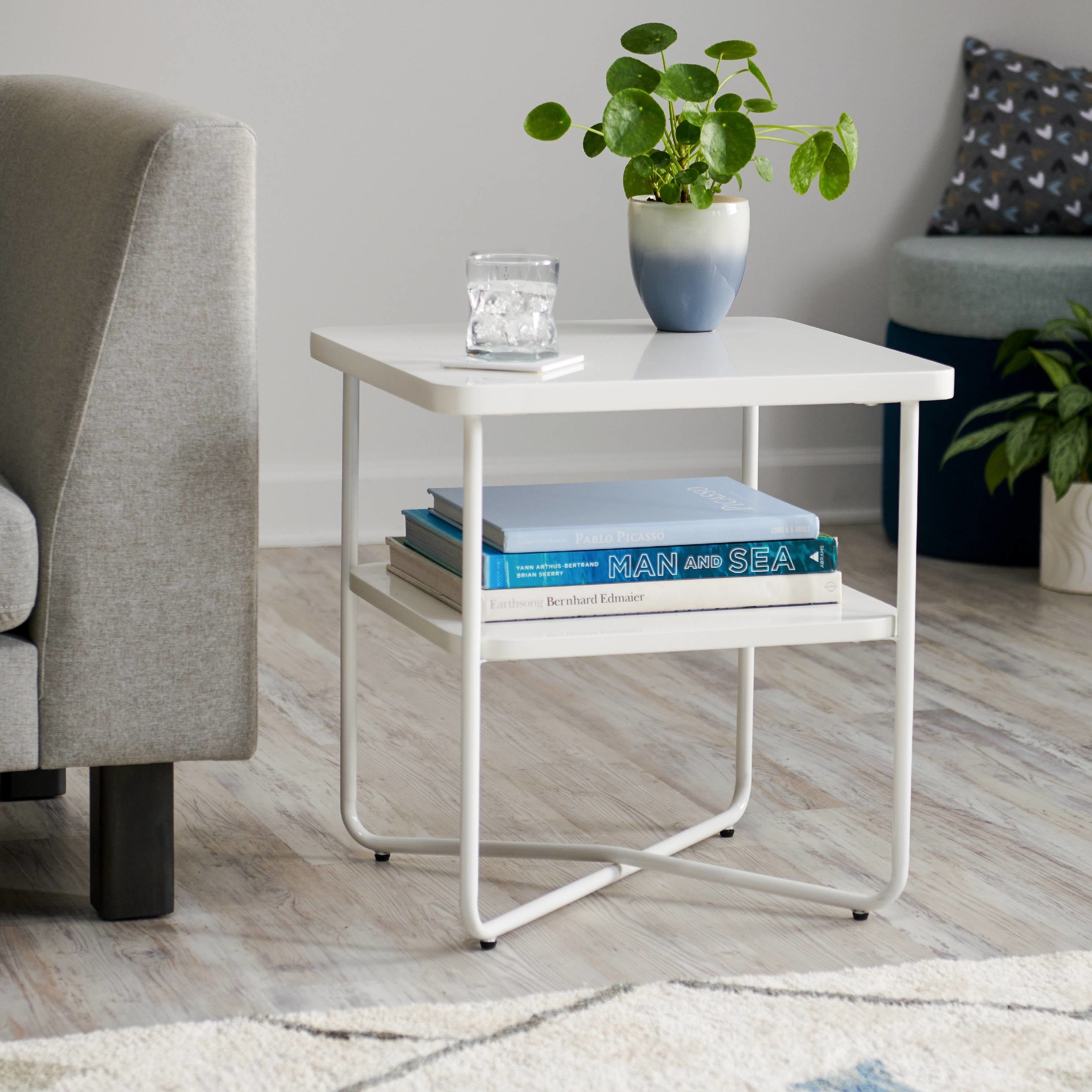 """The table, which has two shelves and an """"X"""" base, in white"""