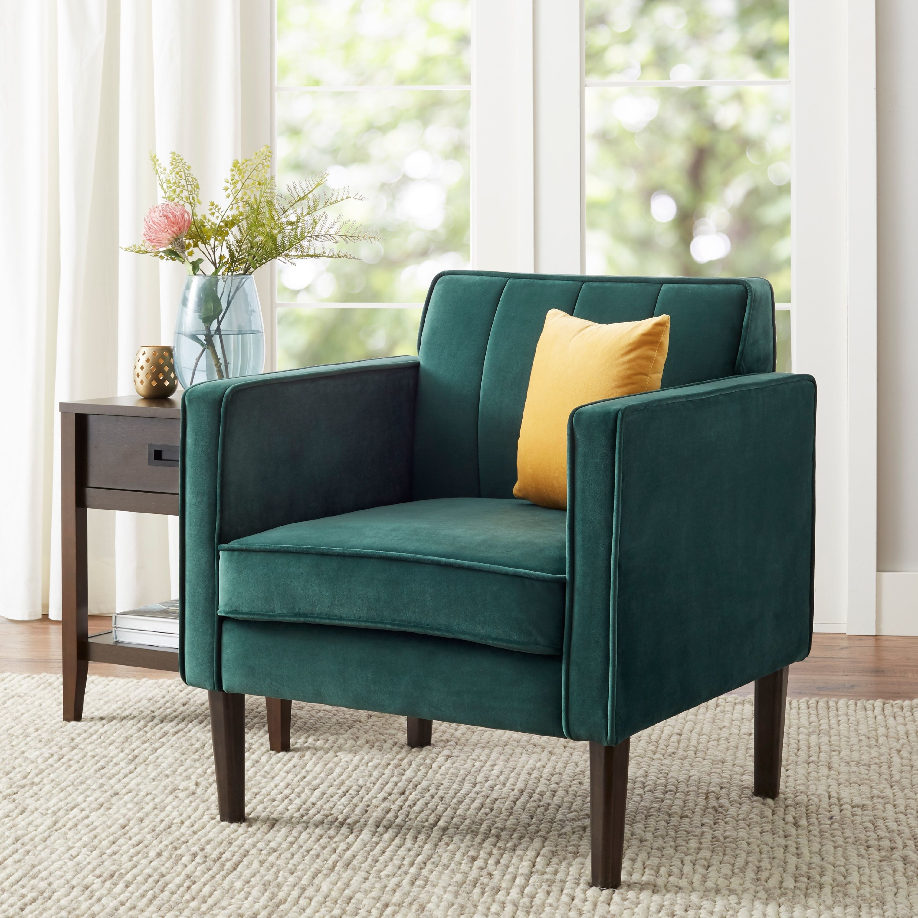The chair, which has a vintage, midcentury look with a high square back and large square sidepiece armrests, in emerald