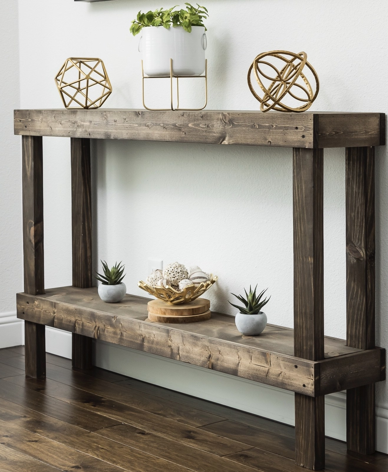 The table, which has a raw wood look, and one lower open storage shelf
