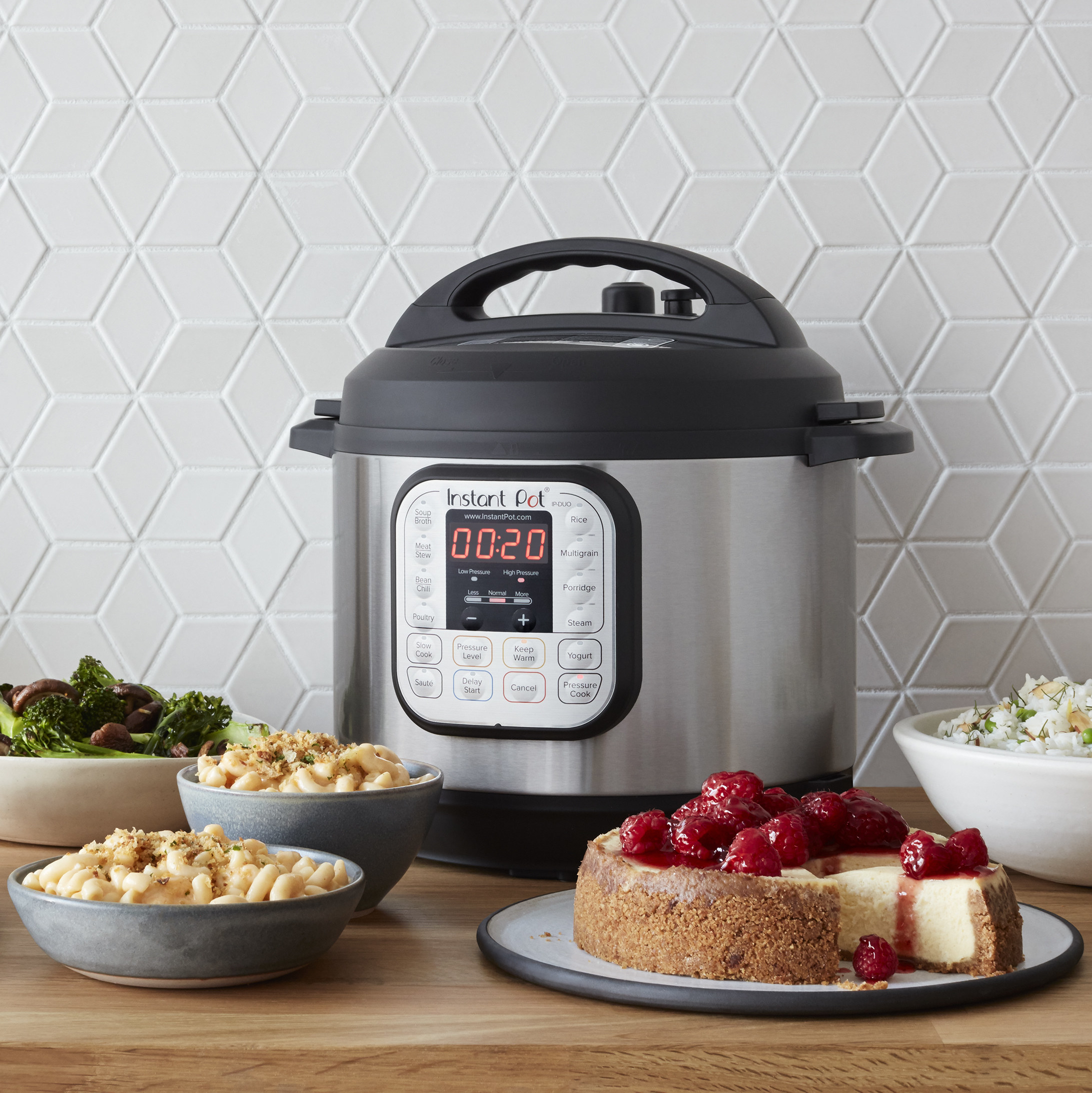 silver instant pot on a table next to vegetables, pasta, and cheesecake