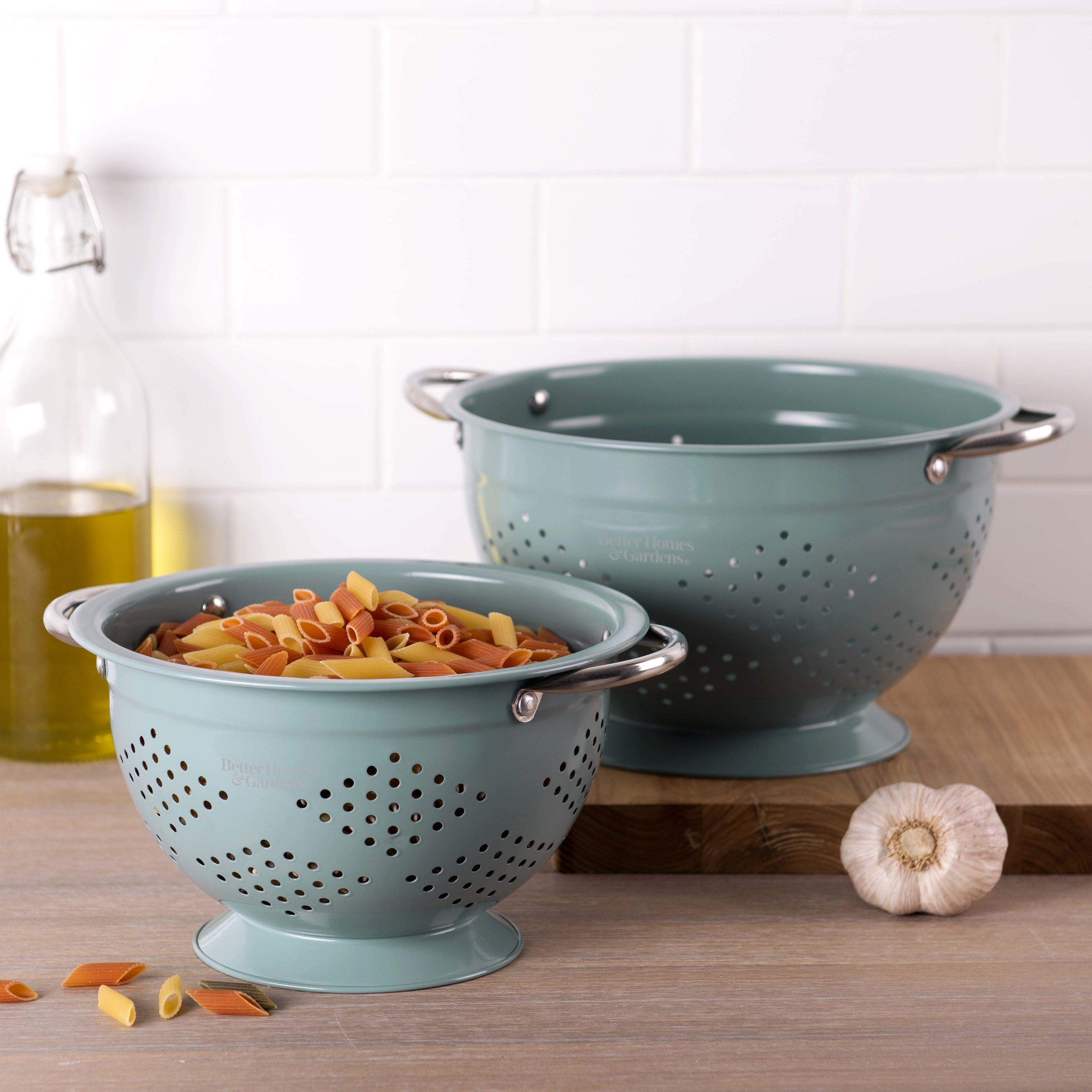 two aqua colored colanders on a counter, one with pasta inside