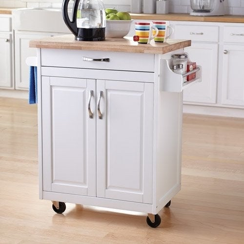 white kitchen island cart with wheels in a kitchen, with pitcher, bowl, and top
