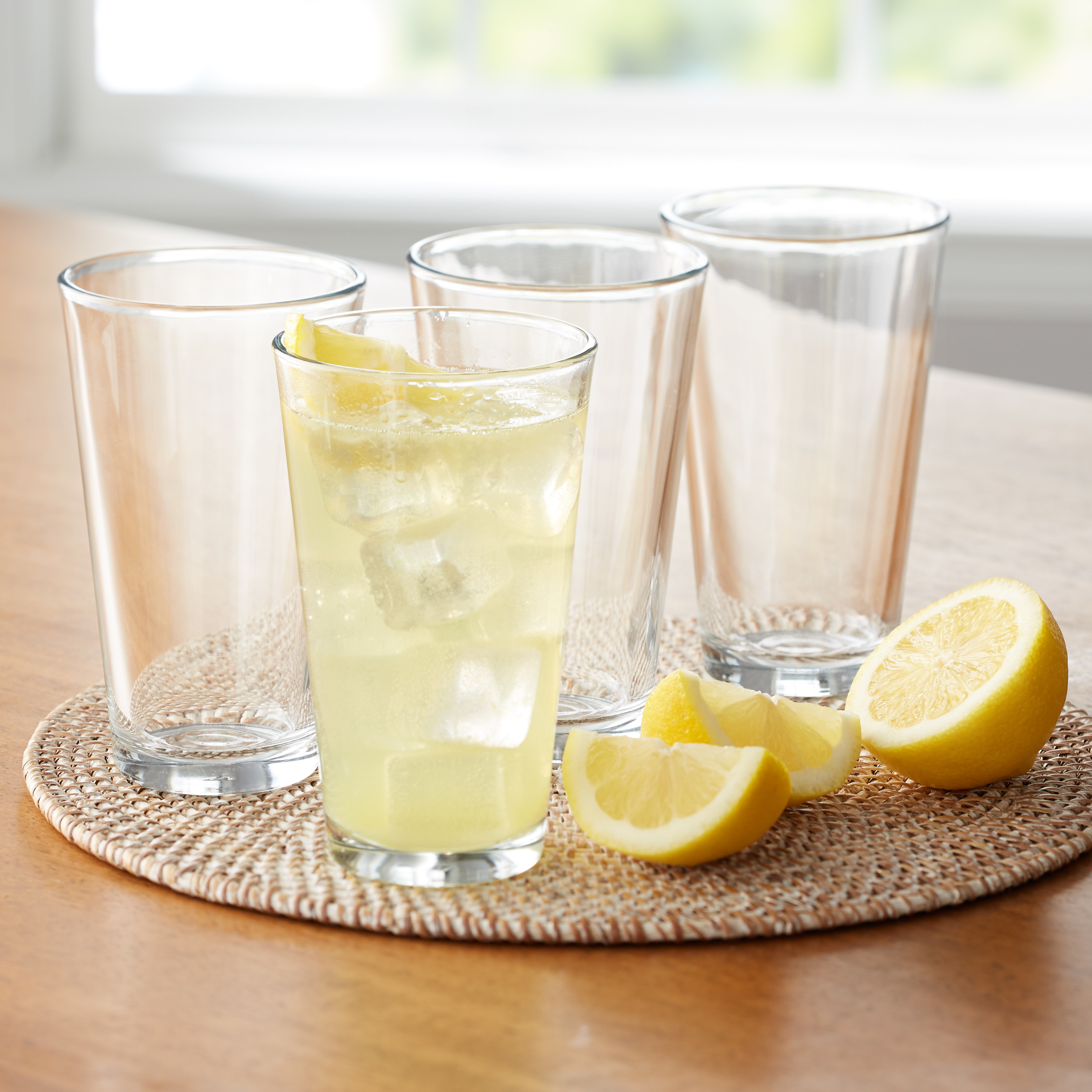 Four glasses on a table, one filled with lemonade, sitting next to a sliced lemon
