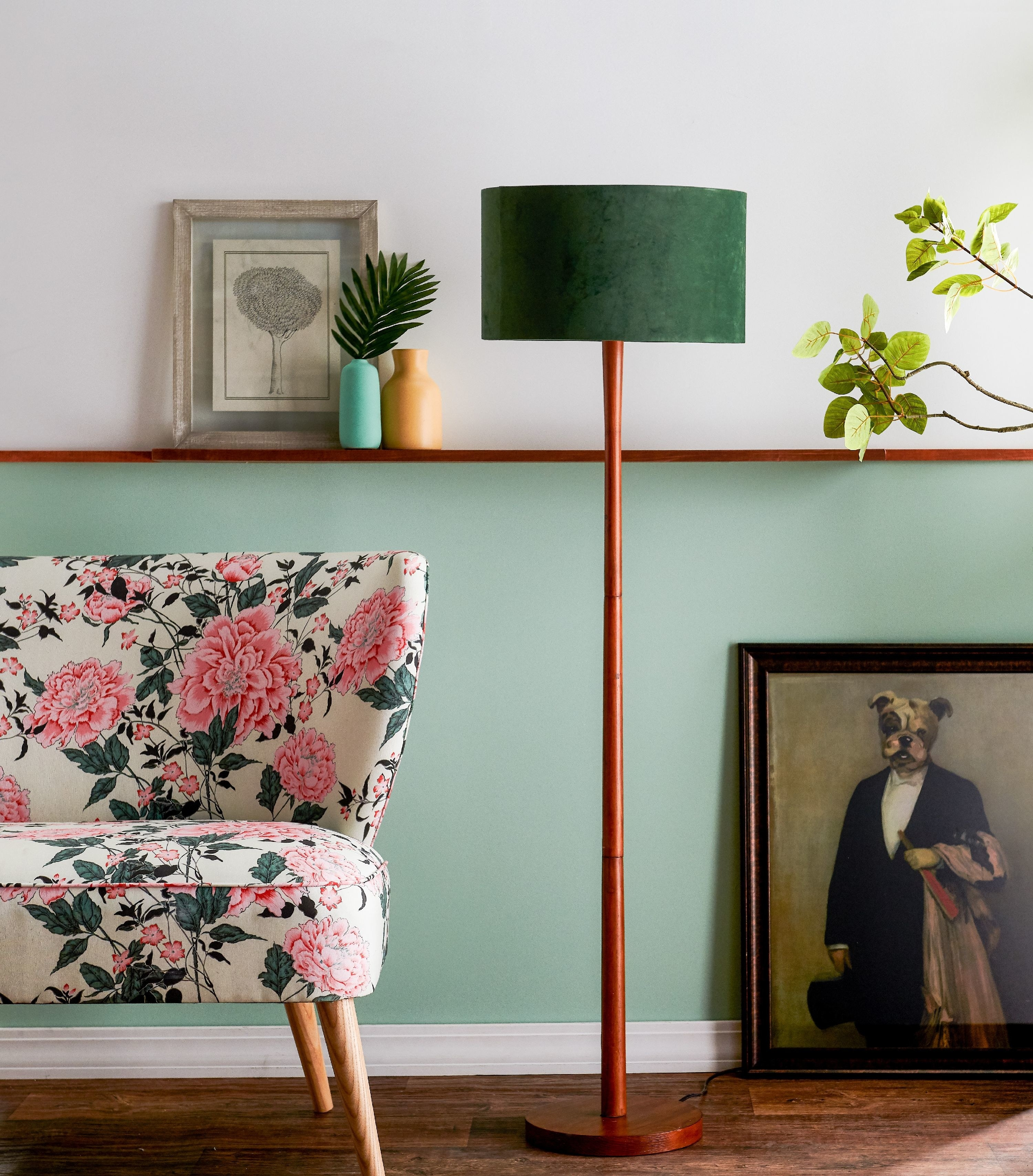 The lamp, which has a round base, slim rod body, and green velvet drum shade