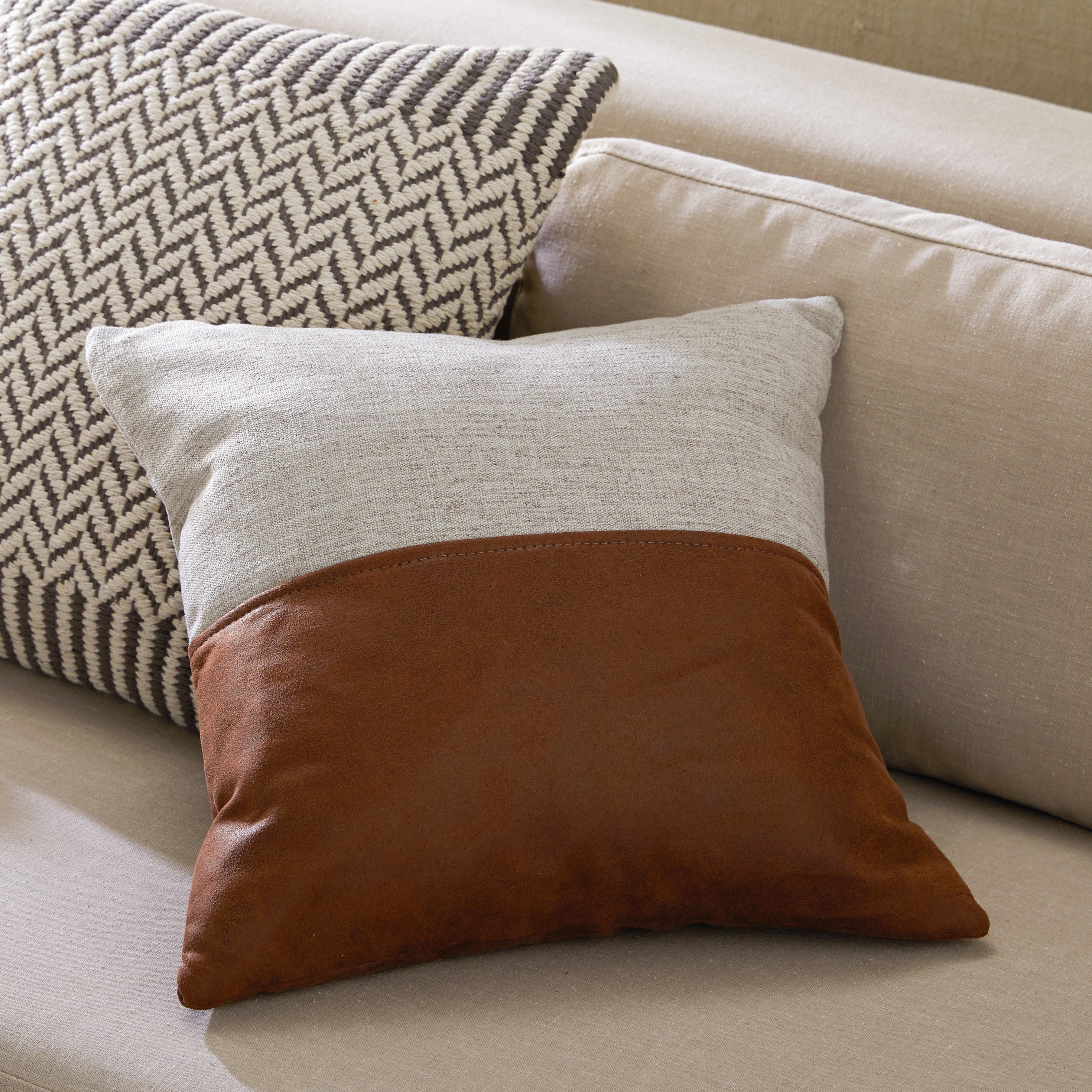 The pillow, which is square and has gray woven fabric on one half, and reddish-brown leather on the other
