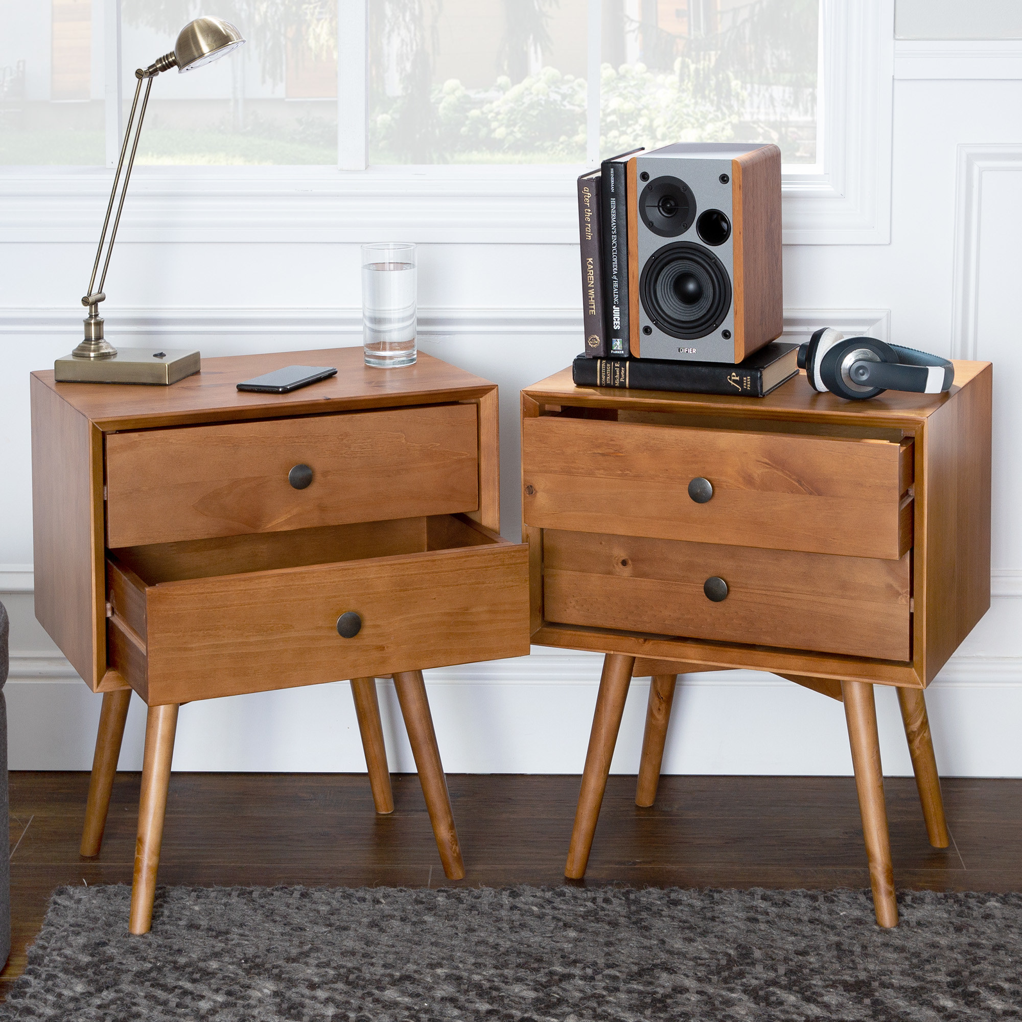 The two nightstands, which have four thin splayed legs, two drawers each, and a low, rectangular silhouette