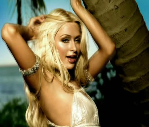 Paris Hilton dances near a palm tree