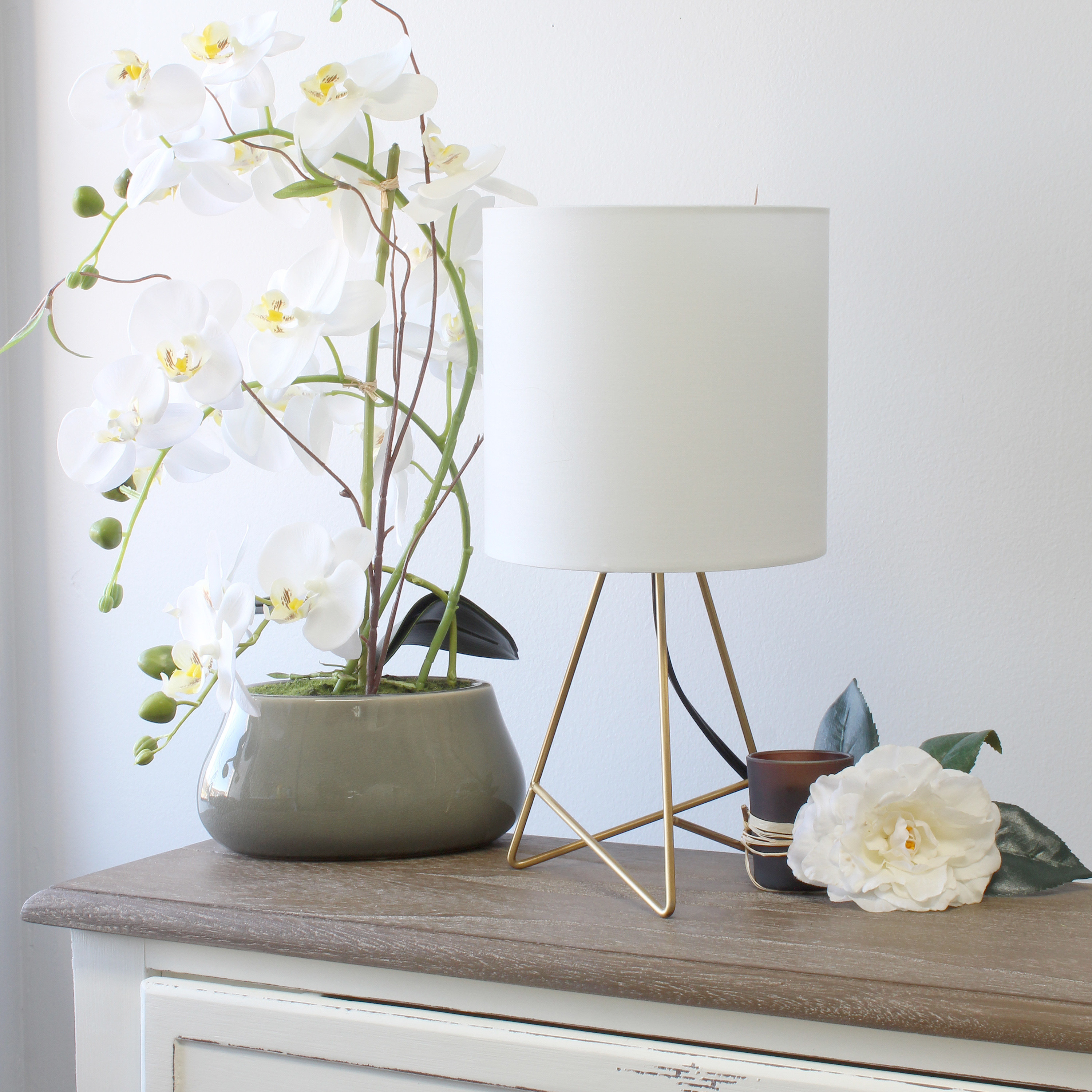 The lamp, which has a white drum shade and a base comprised of two triangular wire panels