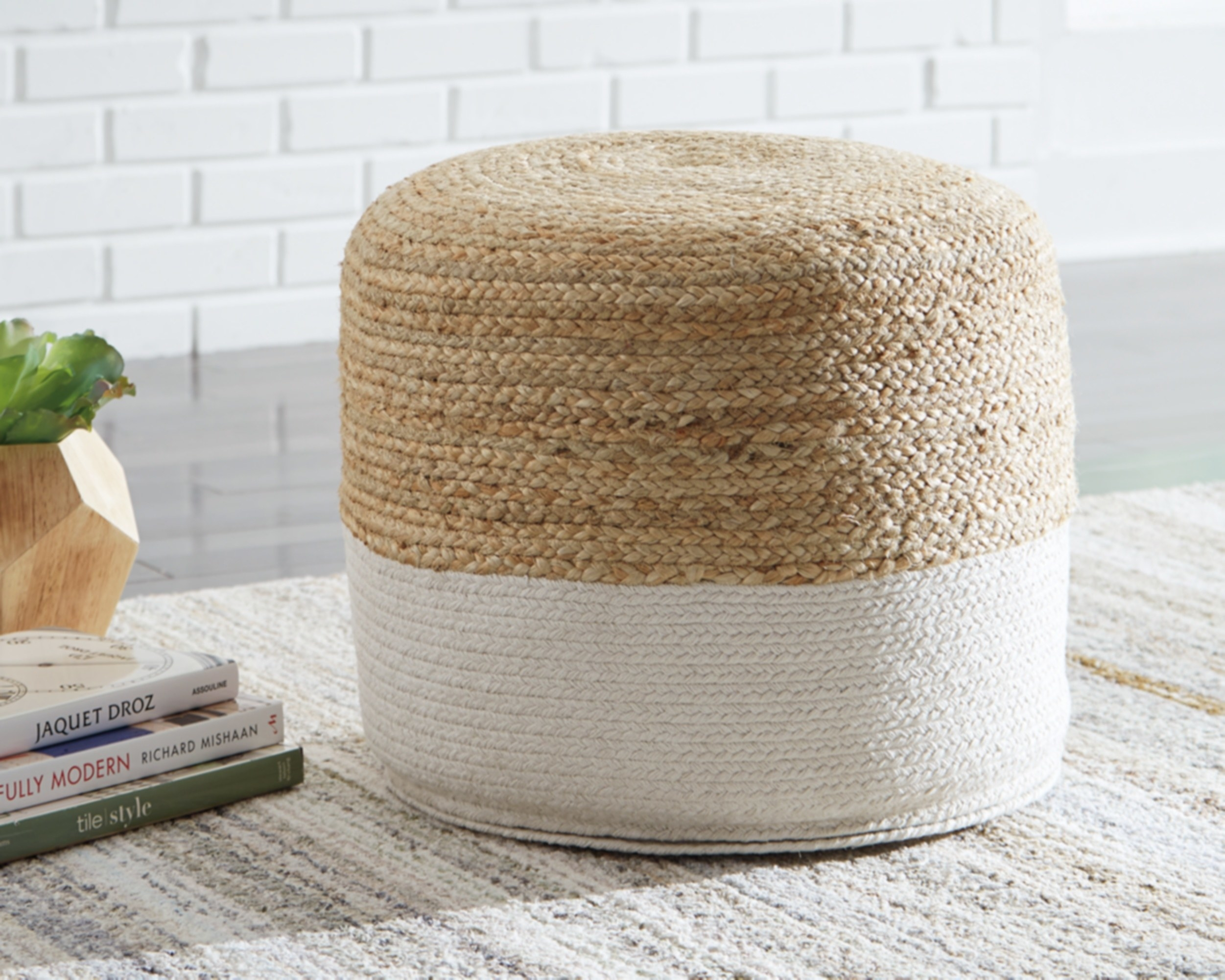 The pouf, which is cylindrical with a rounded top, and which is half white braided cotton, half  braided jute in a natural tone