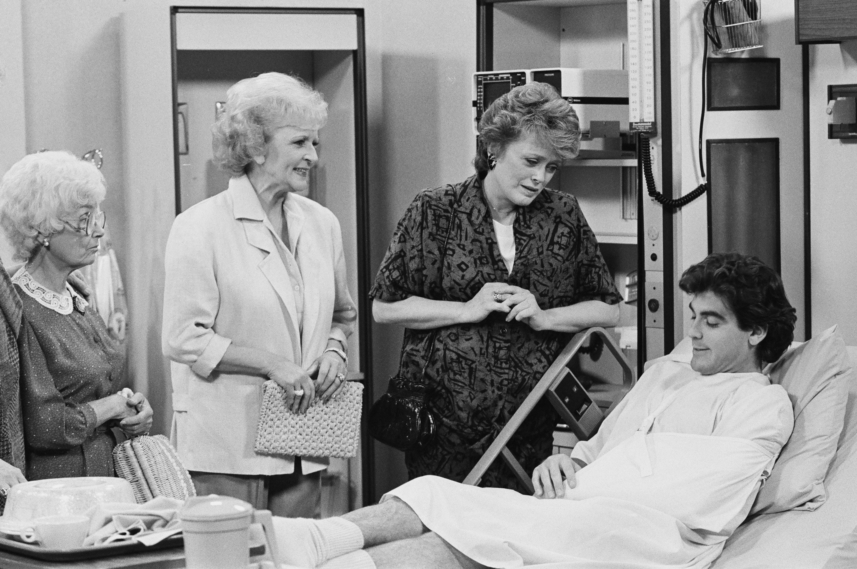 George Clooney laying in a hospital bed surround by Estelle Getty, Betty White, and Rue McClanahan