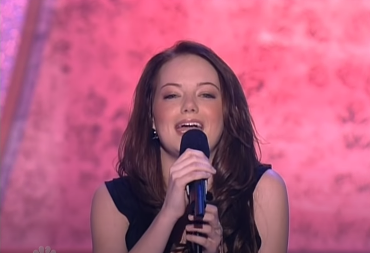 Emma Stone singing on a stage with a pink background behind her.
