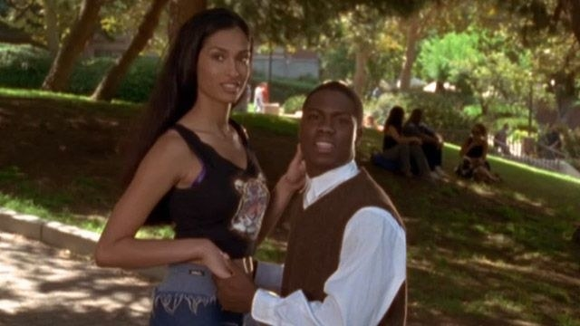 Kevin Hart in a sweater vest holding a tall woman's hand on a college campus