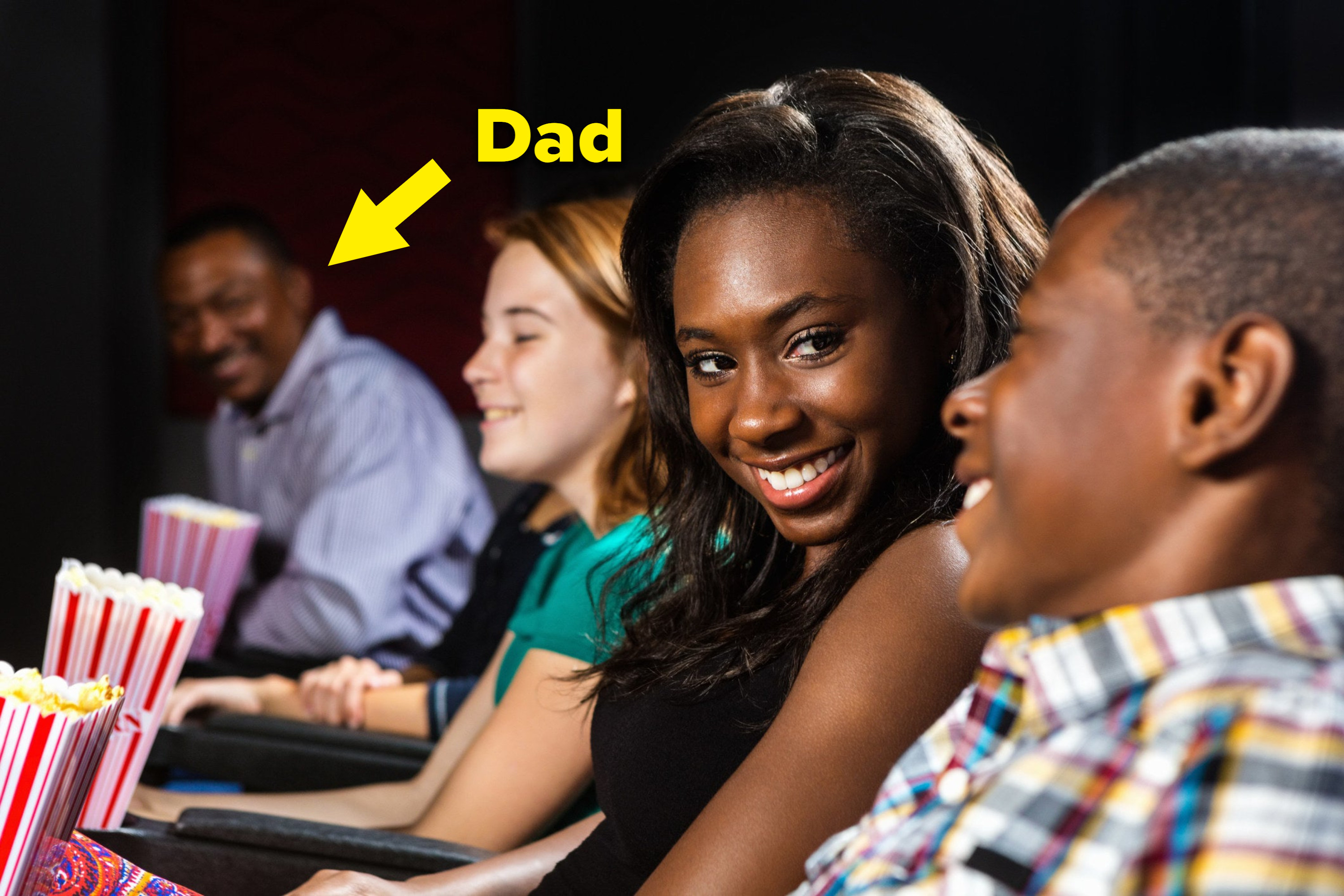 Two teens sit together in a movie as the girl's dad looks on