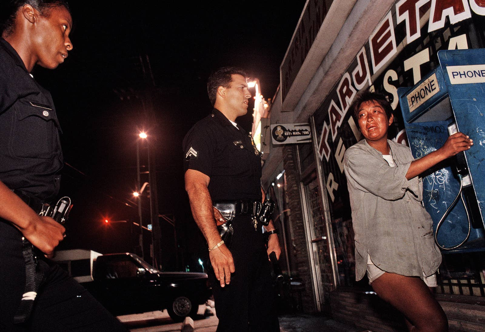 A woman crying at a phone booth while two cops talk with her