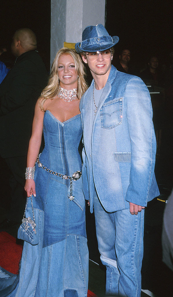 Britney wearing a full-length denim dress with a train, a chain belt, and matching denim clutch while posing with Justin, who's wearing a denim suit and matching denim cowboy hat