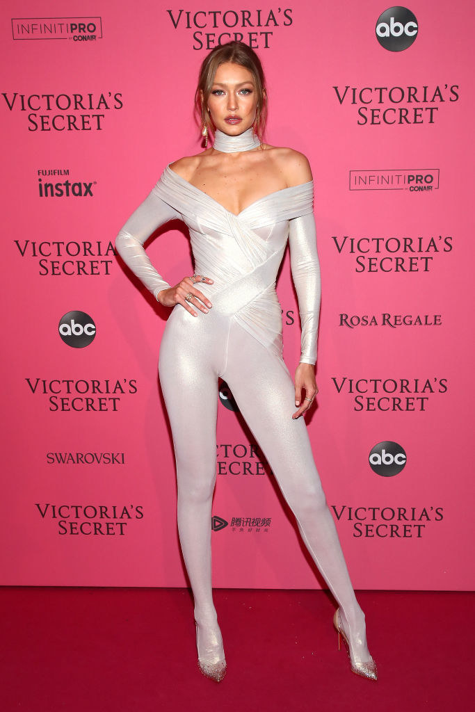 Gigi wearing an off-the-shoulder body suit and heels on the Victoria's Secret red carpet in 2018