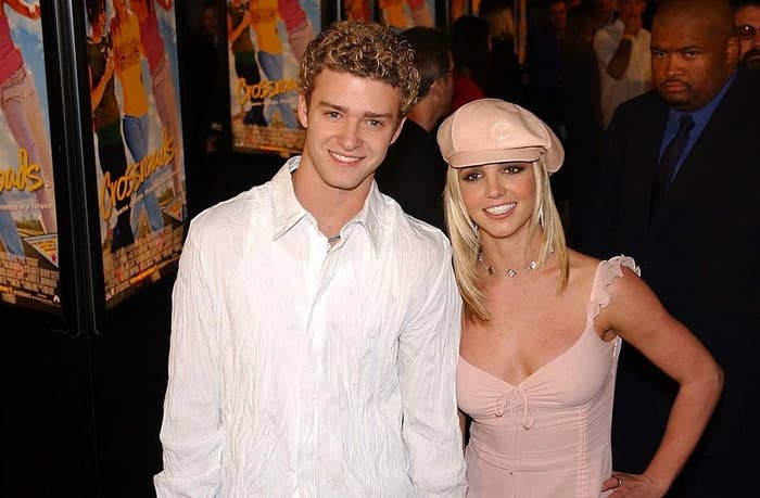 Justin and Britney posing on a red carpet with signs for her movie Crossroads in the background