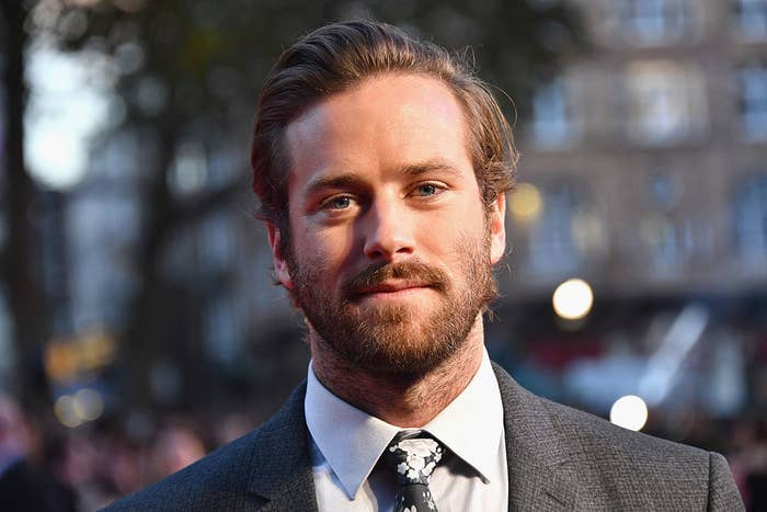 Armie with a full beard and black and white suit