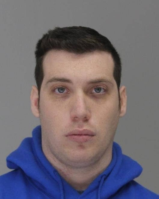 A mugshot of a white man in a blue hoodie
