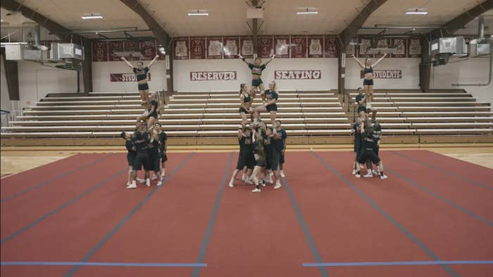 Three groups of cheerleaders in formation inside a gym