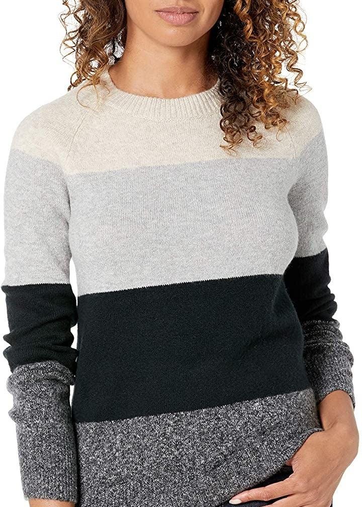 Model wearing the grey multi-stripe sweater