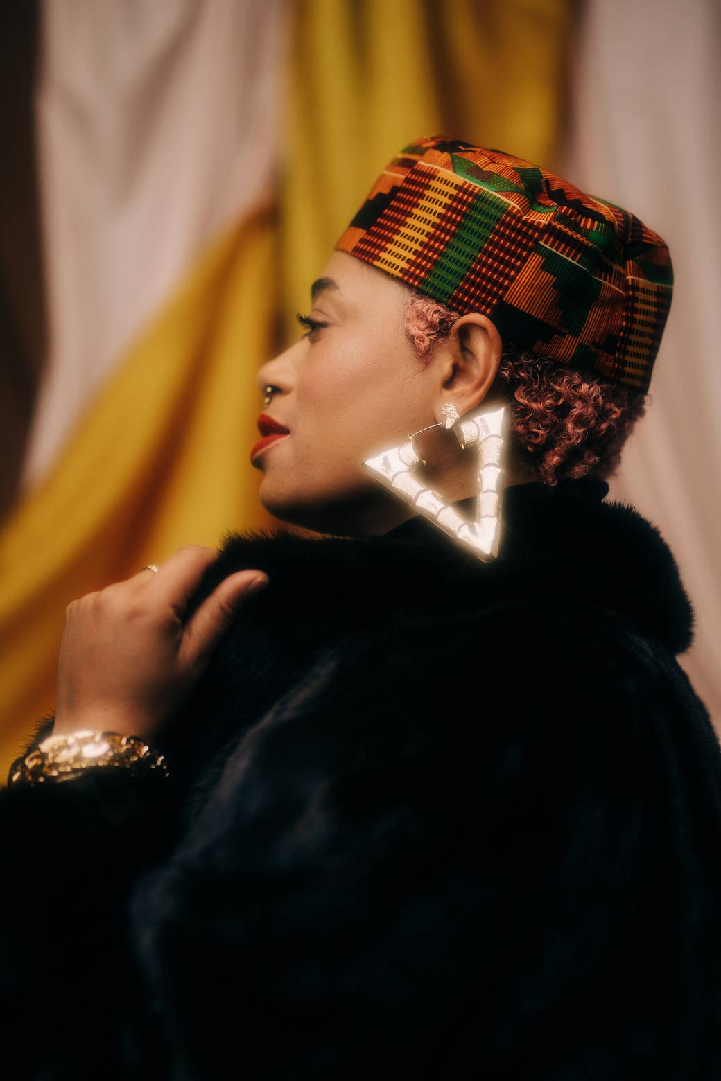 A woman wearing a hat in traditional African print, a black fur coat, and giant gold triangle earrings looks off in the distance.