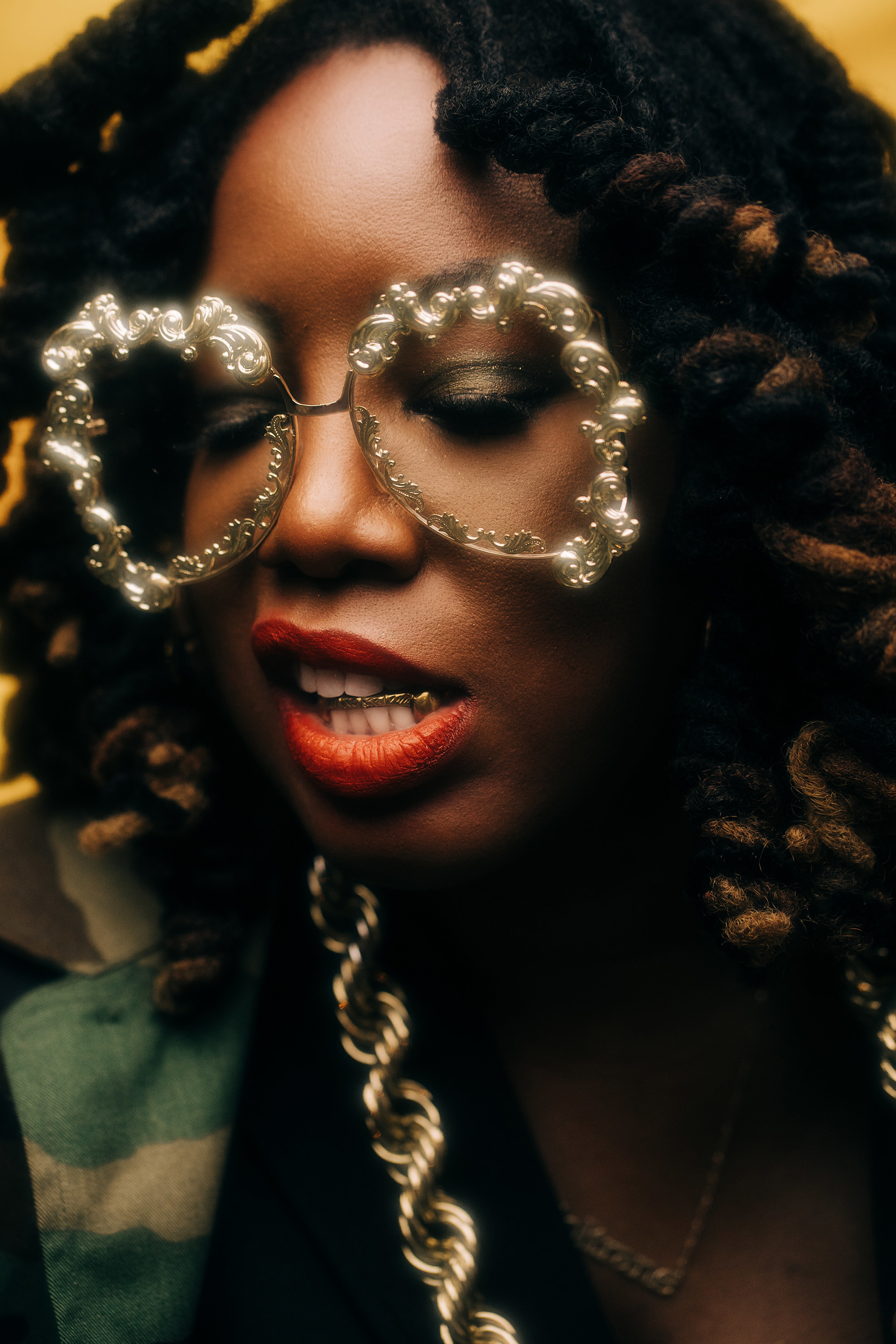 A woman with a god bar in her teeth and giant gold filigree glasses and red liptsick looks down in a portrait.