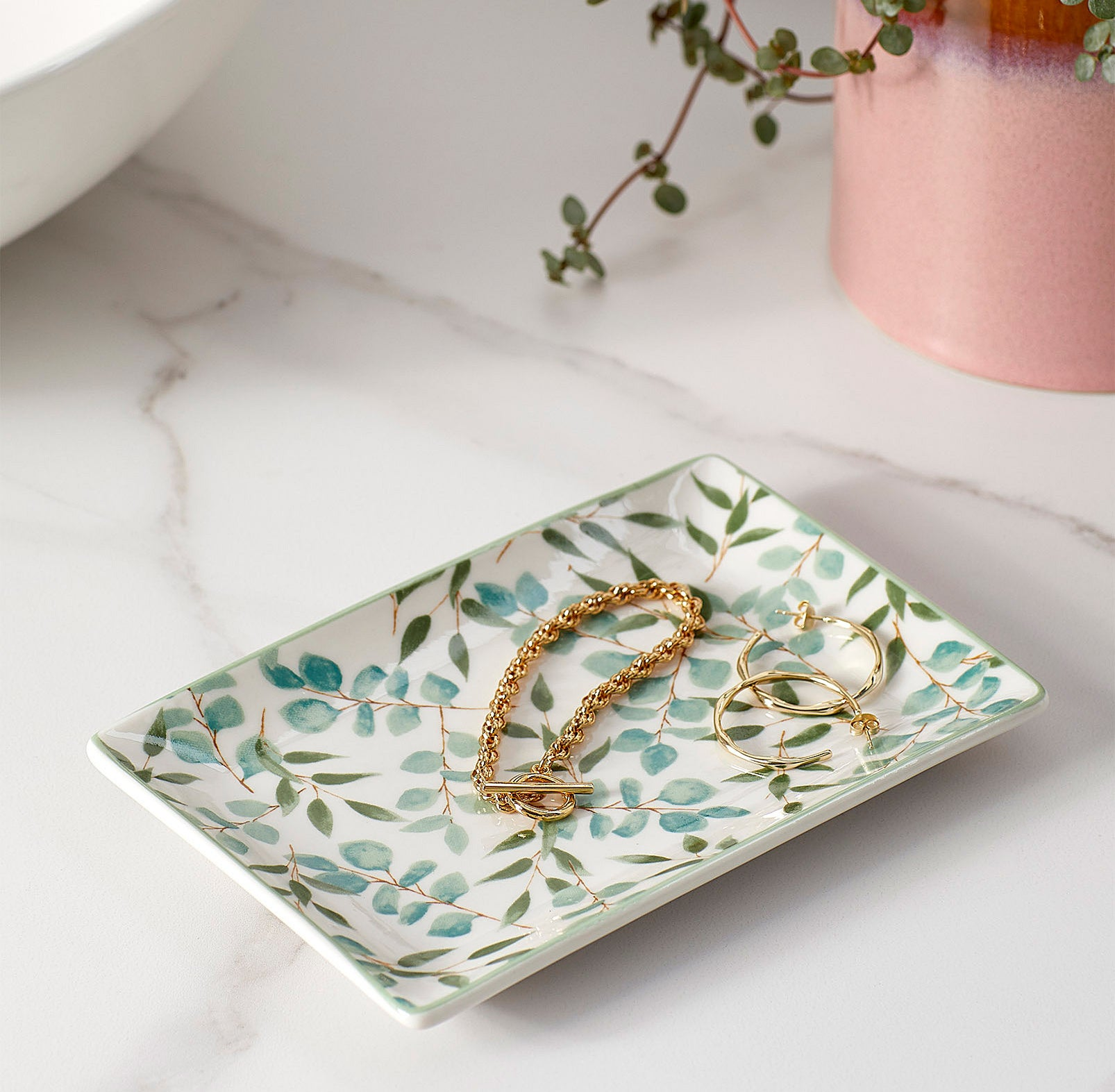 A cute patterned tray with jewelry on it