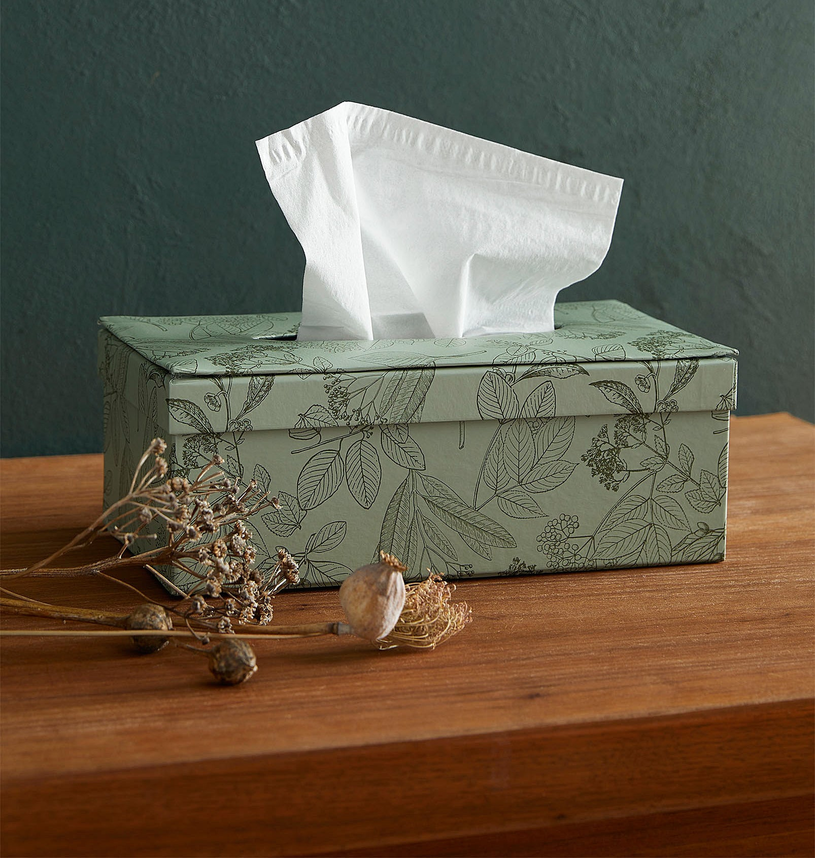 A tissue box holder with a tissue sticking out of it