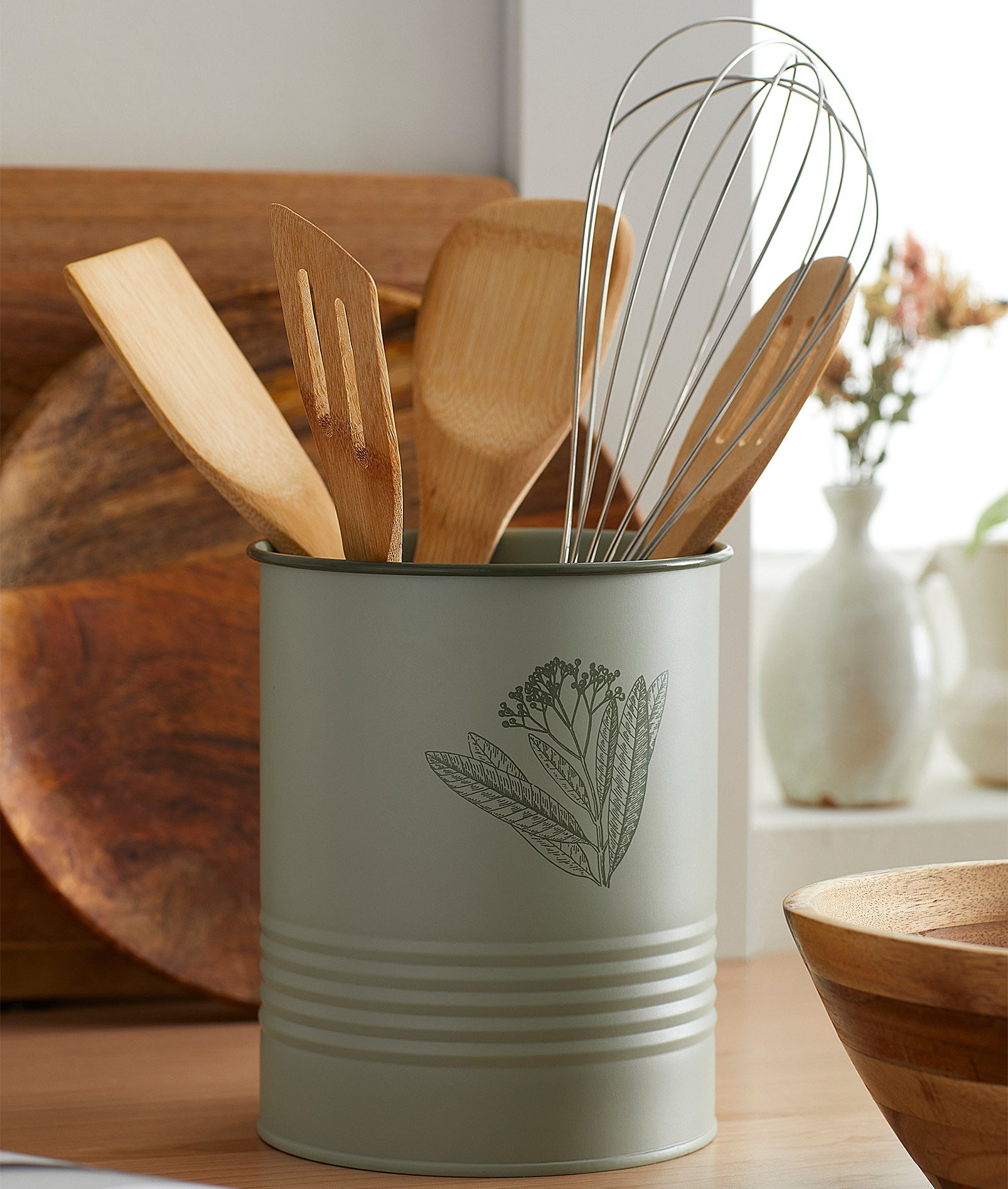 A cute canister with a flower on it holding ladles and spatulas