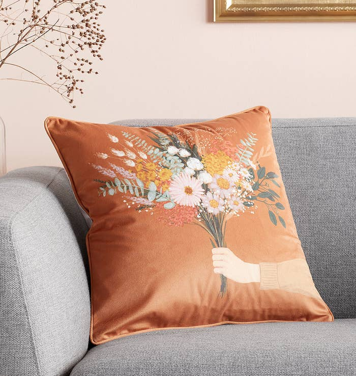 A floral throw pillow on a couch