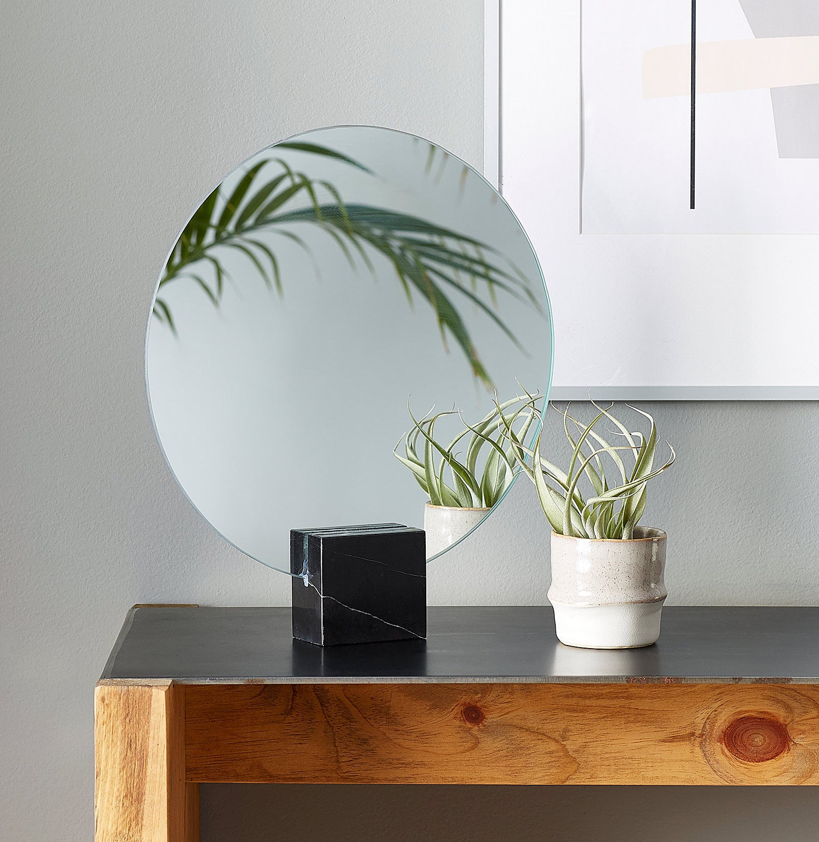 A round mirror sitting in a marble cube next to a small plant
