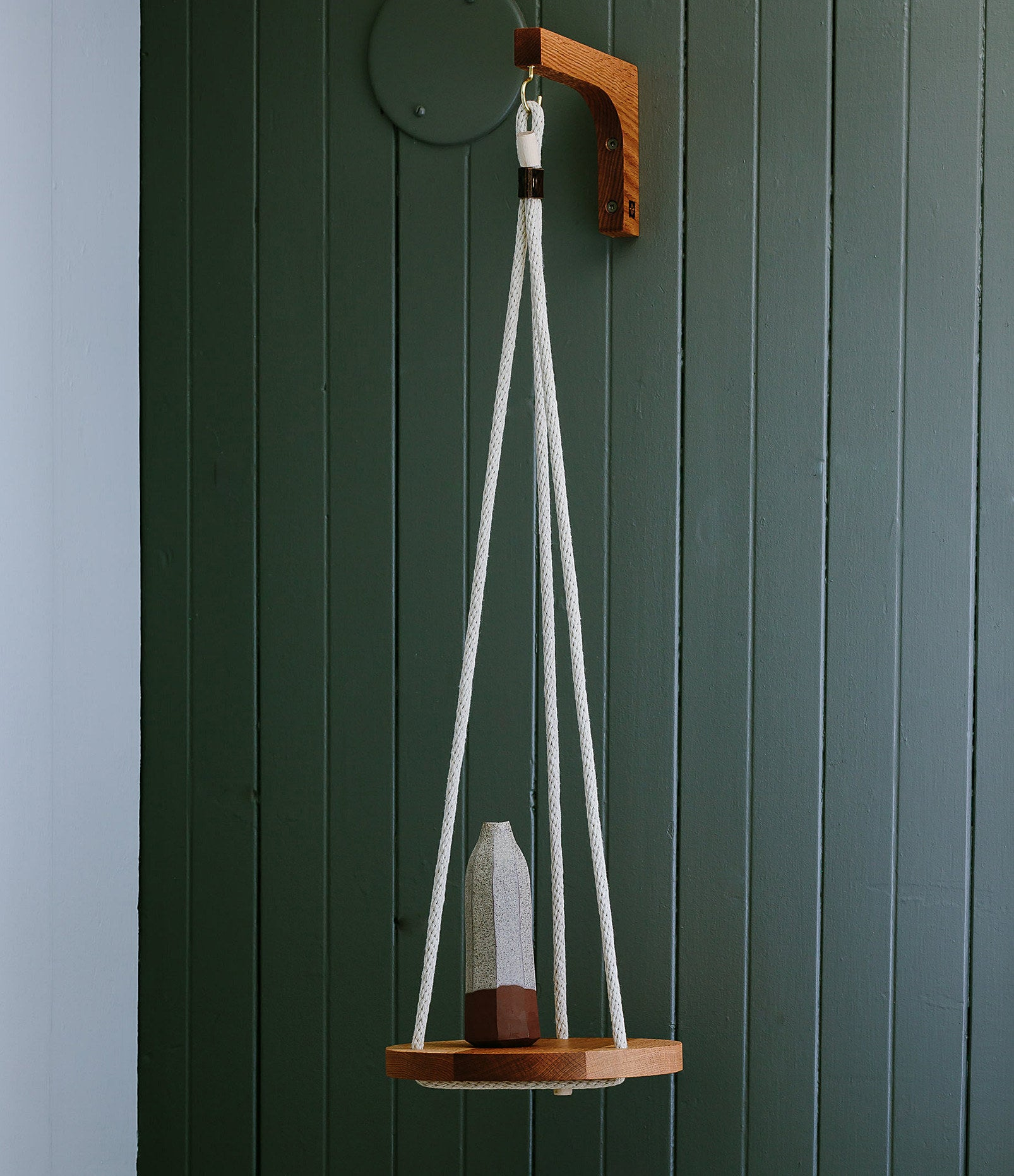 A hanging shelf with a decorative vase sitting on it
