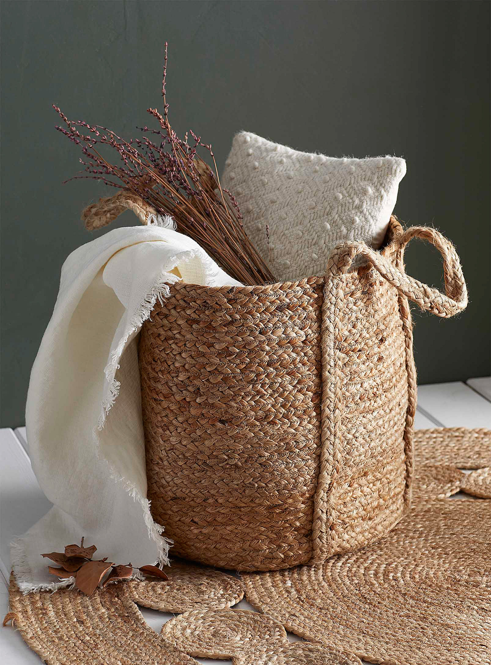 A woven basket with blankets and pillows inside