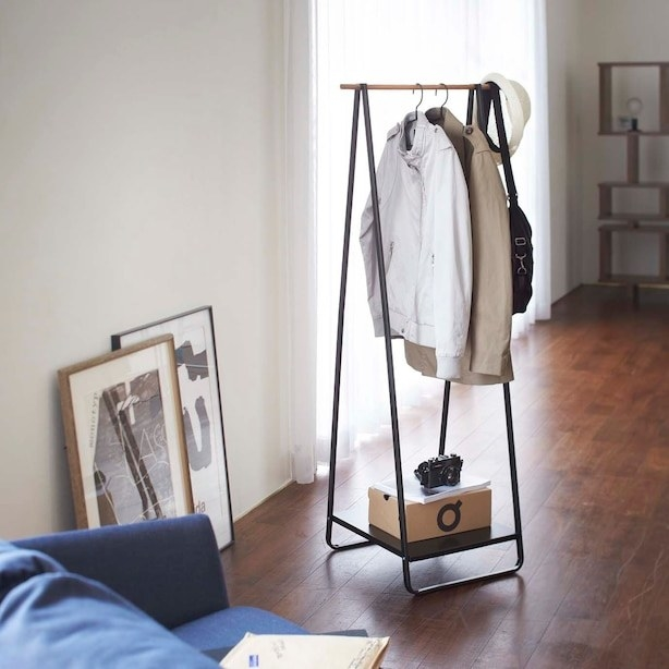 The stand with clothes hanging off of it and a box sitting on the lower shelf
