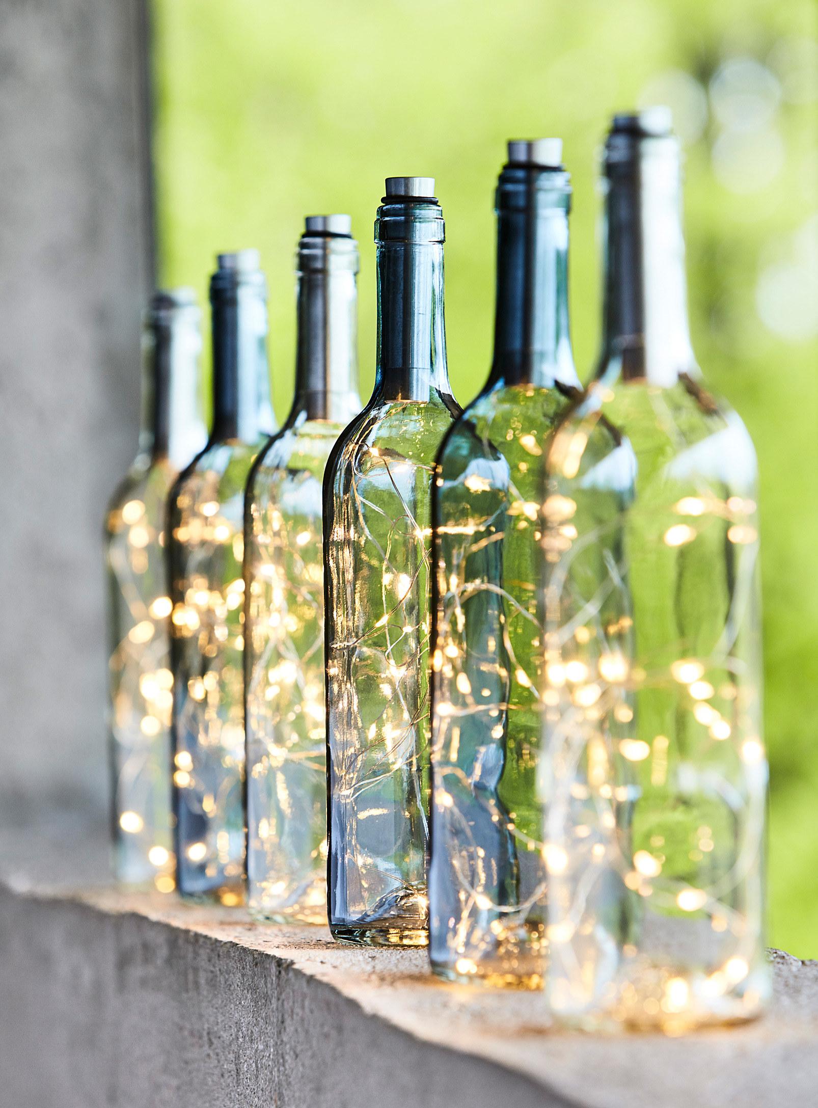 Six glass bottle lanterns sitting in a row