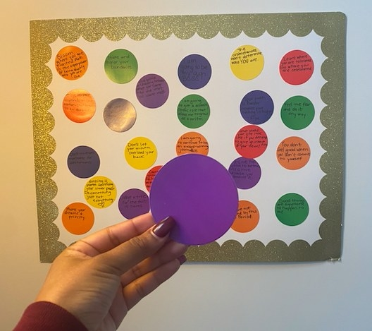 A manicured hand is holding up a paper cutout of a circle in front of a large piece of paper on the wall with quotes.