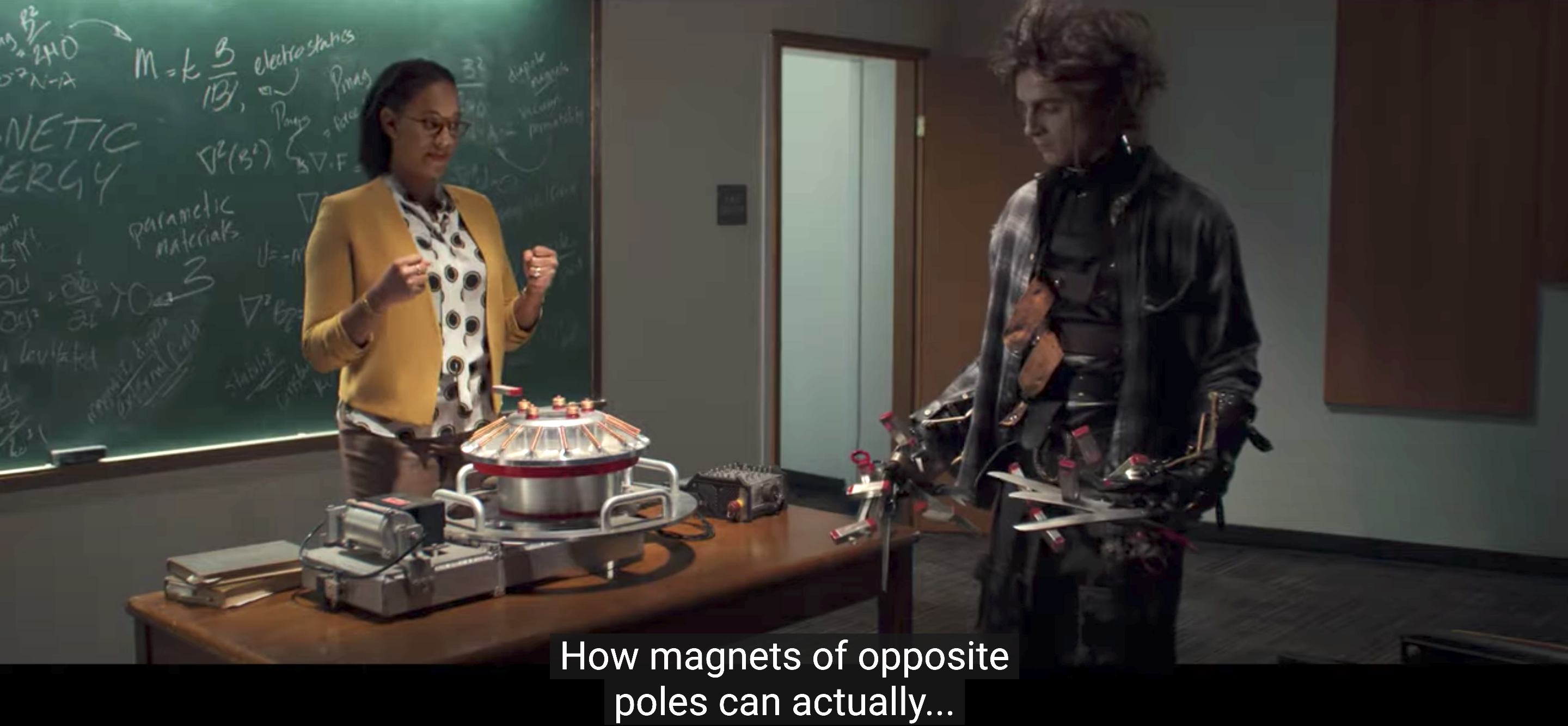 Edgar standing in a classroom with magnets attached to his scissorhands